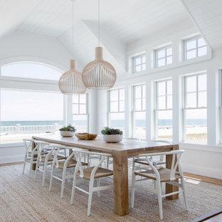 Maritimes Esszimmer mit weißer Wandfarbe, braunem Holzboden und braunem Boden in New York