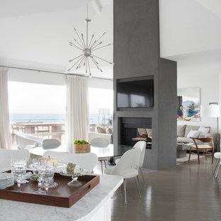 Foto de comedor actual, abierto, con paredes blancas, suelo de madera en tonos medios, chimenea de doble cara y marco de chimenea de hormigón