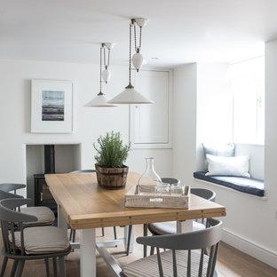 Ejemplo de comedor costero con paredes blancas, suelo de madera clara y estufa de leña