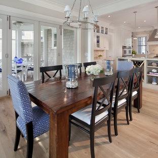 Foto de comedor de cocina costero, grande, sin chimenea, con paredes grises y suelo de madera clara