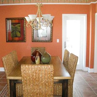Geschlossenes, Mittelgroßes Tropisches Esszimmer mit oranger Wandfarbe und Terrakottaboden in Miami