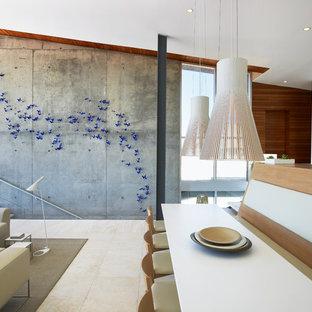 Cette image montre une salle à manger ouverte sur le salon minimaliste avec un mur blanc.