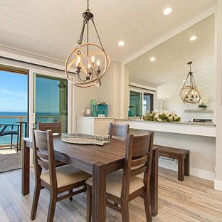 Idée de décoration pour une salle à manger ouverte sur le salon marine de taille moyenne avec un mur gris, un sol en vinyl, une cheminée standard, un manteau de cheminée en carrelage et un sol gris.