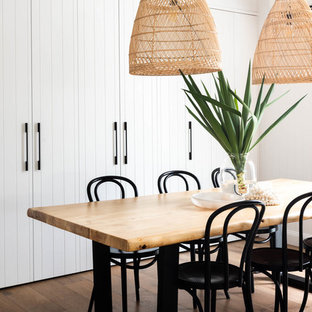 This is an example of a coastal dining room in Brisbane with white walls, medium hardwood flooring and brown floors.