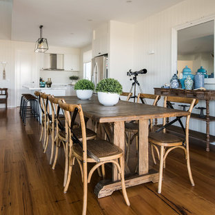 Beach style open plan dining in Melbourne with white walls, medium hardwood floors and brown floor.