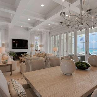 На фото: огромная столовая в морском стиле с белыми стенами, полом из травертина, камином и фасадом камина из плитки с