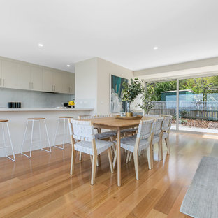 Photo of a beach style open plan dining in Hobart with grey walls, medium hardwood floors and beige floor.