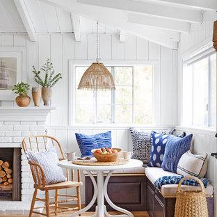 Идея дизайна: маленькая столовая в морском стиле с белыми стенами, светлым паркетным полом, стандартным камином и фасадом камина из кирпича