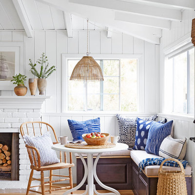 Example of a small beach style light wood floor dining room design in Los Angeles with white walls, a standard fireplace and a brick fireplace