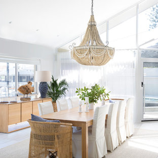 This is an example of a large beach style dining room in Gold Coast - Tweed with white walls, carpet and grey floor.