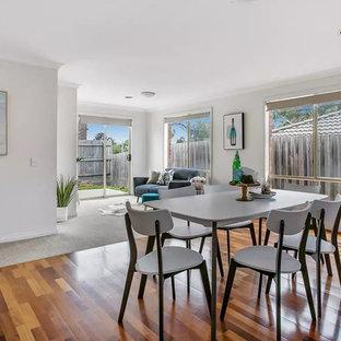 Esempio di una sala da pranzo aperta verso il soggiorno tropicale di medie dimensioni con pareti bianche, pavimento in laminato e pavimento marrone