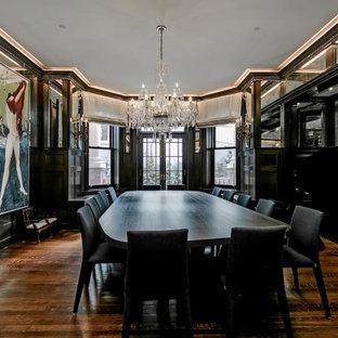 Ispirazione per una grande sala da pranzo vittoriana chiusa con pareti nere, parquet scuro, stufa a legna, cornice del camino piastrellata e pavimento marrone