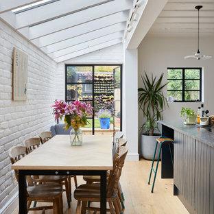 Idee per una sala da pranzo aperta verso la cucina minimal con pareti bianche, parquet chiaro, pavimento beige e pareti in mattoni