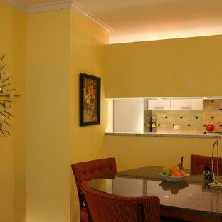 Foto di una piccola sala da pranzo moderna chiusa con pavimento con piastrelle in ceramica, pareti gialle e nessun camino