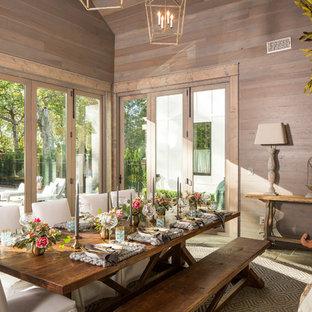Inredning av en lantlig stor separat matplats, med bruna väggar, skiffergolv, en standard öppen spis, en spiselkrans i tegelsten och grått golv