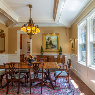 This is an example of a traditional dining room in Charlotte with yellow walls, dark hardwood flooring and brown floors.