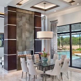 Esempio di una sala da pranzo design con camino bifacciale e pareti bianche