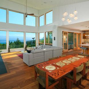 Esempio di una sala da pranzo aperta verso il soggiorno moderna di medie dimensioni con pareti bianche, pavimento in legno massello medio, camino classico e cornice del camino in cemento