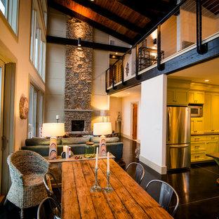 バーミングハムの大きいラスティックスタイルのおしゃれなLDK (ベージュの壁、黒い床、コンクリートの床、標準型暖炉、石材の暖炉まわり) の写真