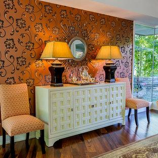 Idee per un'ampia sala da pranzo aperta verso la cucina moderna con pareti arancioni e parquet scuro