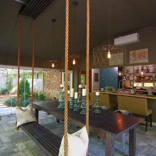 Esempio di una sala da pranzo aperta verso la cucina chic di medie dimensioni con pareti marroni, pavimento in mattoni, nessun camino e pavimento grigio