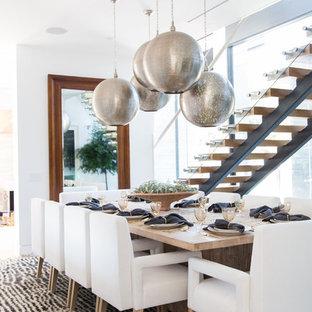 Идея дизайна: большая отдельная столовая в современном стиле с белыми стенами, полом из известняка, двусторонним камином и фасадом камина из плитки