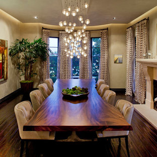 Example of a tuscan dark wood floor enclosed dining room design in Los Angeles with beige walls, a standard fireplace and a plaster fireplace