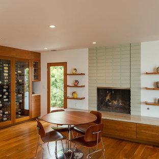 Inspiration pour une salle à manger ouverte sur la cuisine minimaliste de taille moyenne avec un manteau de cheminée en béton, un mur blanc, un sol en bois foncé, une cheminée standard et un sol marron.