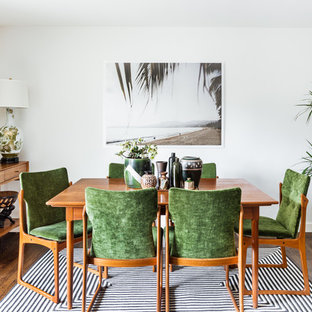 Example of an island style medium tone wood floor dining room design in Seattle with white walls
