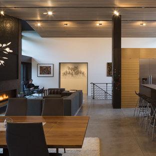 Foto på en stor retro matplats med öppen planlösning, med vita väggar, betonggolv, en bred öppen spis och en spiselkrans i gips