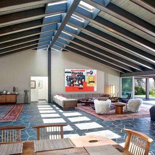 Esempio di una sala da pranzo aperta verso il soggiorno minimalista con pareti beige, pavimento in ardesia, camino classico e cornice del camino in pietra