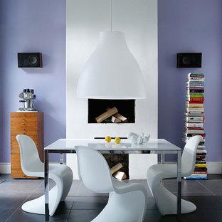 Diseño de comedor bohemio, de tamaño medio, cerrado, con paredes púrpuras, suelo de baldosas de porcelana, chimenea tradicional y marco de chimenea de yeso