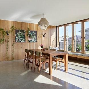 Immagine di una sala da pranzo aperta verso la cucina scandinava con pareti marroni, pavimento in cemento e pavimento grigio