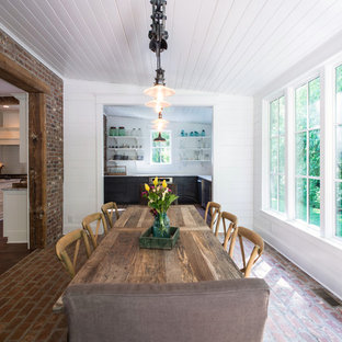 Elegant brick floor dining room photo in Nashville with white walls