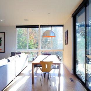 Diseño de comedor moderno, de tamaño medio, abierto, sin chimenea, con paredes blancas, suelo de bambú y suelo marrón