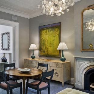 Idee per una piccola sala da pranzo aperta verso il soggiorno design con cornice del camino in pietra, pareti grigie e camino classico