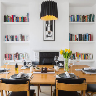 Small contemporary dining room in London with white walls and a standard fireplace.