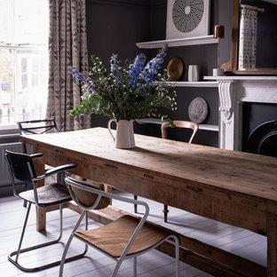 ロンドンのエクレクティックスタイルのおしゃれなダイニング (黒い壁、塗装フローリング、標準型暖炉、石材の暖炉まわり、グレーの床) の写真