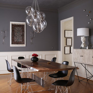 Inspiration for a contemporary medium tone wood floor enclosed dining room remodel in Raleigh with gray walls