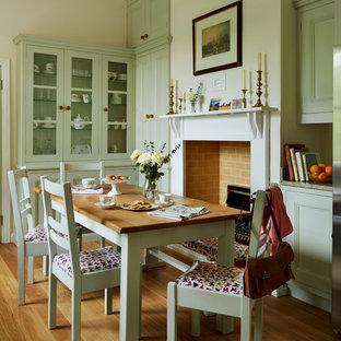 他の地域の中サイズのトラディショナルスタイルのおしゃれなダイニングキッチン (ベージュの壁、無垢フローリング、標準型暖炉、木材の暖炉まわり) の写真