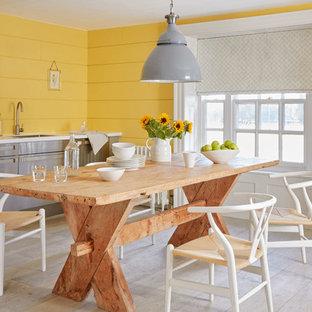 Imagen de comedor de cocina campestre, de tamaño medio, con paredes amarillas, suelo gris y suelo de madera clara