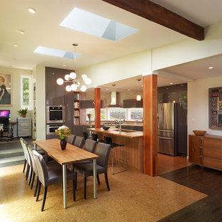На фото: кухня-столовая среднего размера в современном стиле с белыми стенами, пробковым полом и коричневым полом без камина с