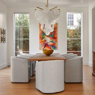 Esempio di una sala da pranzo chic chiusa e di medie dimensioni con pareti bianche, pavimento in legno massello medio, pavimento marrone e nessun camino