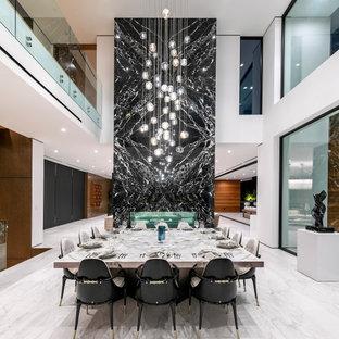 На фото: огромная гостиная-столовая в современном стиле с белыми стенами, двусторонним камином, фасадом камина из плитки и серым полом с