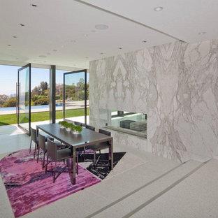 Ejemplo de comedor minimalista, de tamaño medio, abierto, con paredes blancas, suelo de cemento, chimenea de doble cara, marco de chimenea de baldosas y/o azulejos y suelo blanco
