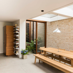Photo of a medium sized contemporary dining room in London with beige floors and brown walls.