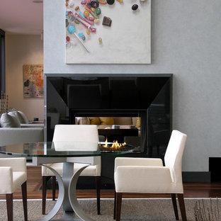 Неиссякаемый источник вдохновения для домашнего уюта: кухня-столовая среднего размера в современном стиле с серыми стенами, темным паркетным полом, двусторонним камином, фасадом камина из штукатурки и коричневым полом