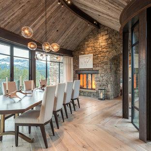 Foto de comedor rural con paredes grises, suelo de madera clara, chimenea de doble cara, marco de chimenea de piedra y suelo beige
