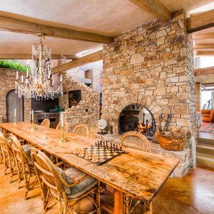 Diseño de comedor de cocina mediterráneo, extra grande, con paredes marrones, suelo de cemento, chimenea de doble cara y marco de chimenea de piedra