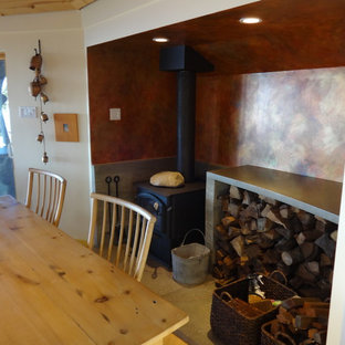 Photo of a beach style dining room in San Francisco with a hanging fireplace and a stone fireplace surround.